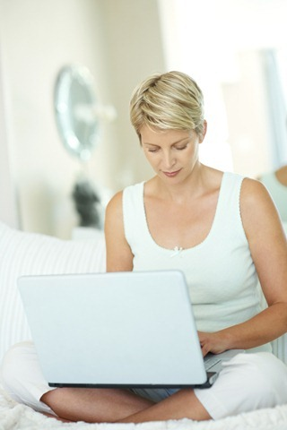 Mature woman using a laptop , sitting on a bed at home