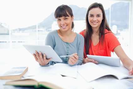 A pair of smiling girls doing work with tablets as they look into the camera